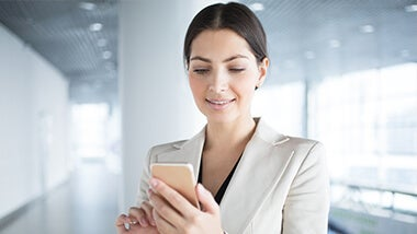 woman smiling looking at her phone