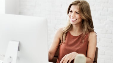 Woman smiling at the computer